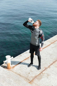 Runner drink water in harbor. from above image