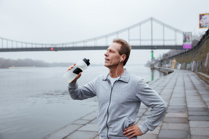 Runner in gray sportswear drink water and standing near the river