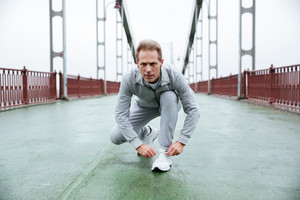 Runner in gray sportswear prepare on bridge. Front view