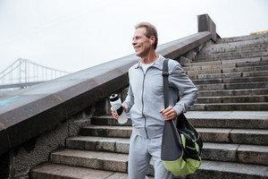 Runner in gray sportswear standing on stairs with bottle of water and bag