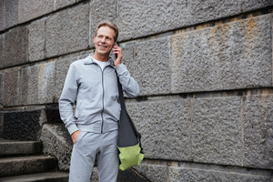 Runner in gray sportswear standing with bag and talking at phone near the stairs
