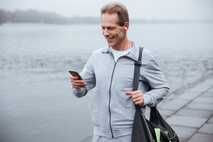 Runner in gray sportswear standing with phone and bag near the river