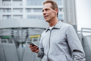 Runner in gray sportswear standing with phone on the street. Side view