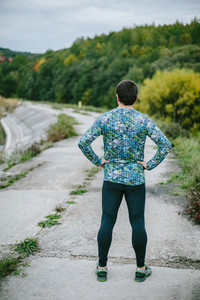 Runner in sportswear resting on an old road in green nature. Cloudy rainy day. Back view, rear view