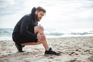 Runner injured. on beach. side view