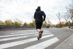 Runner on crosswalk. back view