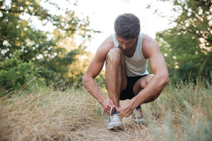 Runner preparing in forest. tying shoelaces
