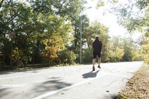 Runner running in park. back view