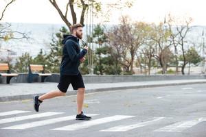 Runner. runs on the street. on crosswalk. full lenght. front photo