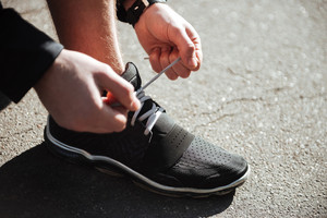 Runner tying shoelaces in park. cropped image