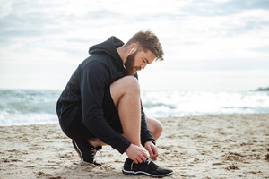 Runner tying shoelaces on beach. side view