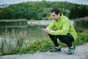 Runner with smart phone and earphones, in yellow neon jacket, on the path at the lake resting against green nature