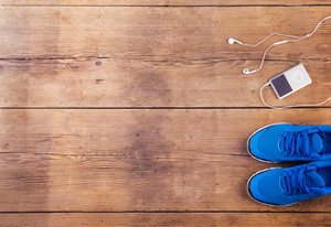 Running shoes and mp3 player on a wooden floor background