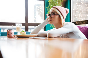 Sad bored young woman in hat and glasses sitting at the table in cafe