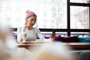 Sad frowning young woman in hat and glasses sitting and using mobile phone in cafe
