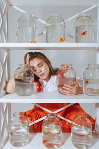 Sad tired young woman sitting and leaning on shelf with gold fishes in jars