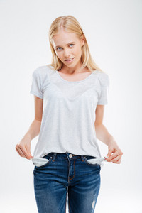 Sad young woman showing empty pockets isolated on a white background