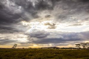 Safari car driving in beautiful and dramatic african landscape
