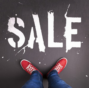 Sale concept with red sneakers and white paint text on black floor