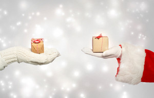 Santa and hand with winter gloves holding gift boxes