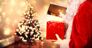 Santa Claus opening a red Christmas present with star shaped lights on a tree