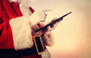 Santa Claus using a digital tablet in vintage style