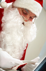 Santa holding Christmas letter and looking at it