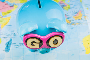 Saving piggy bank from TOP view. GO slogan on sunglasses . Pig is staying on the world map ready for travel