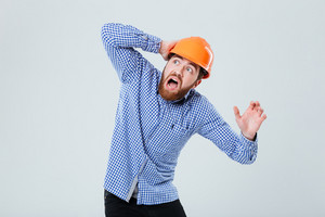 Scared bearded young man in helmet looking up and shouting over white background