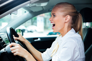Scared business woman driving her car and shouting