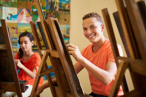 School of art, college of arts, education for group of students. Portraif of happy hispanic young man smiling, looking at camera.