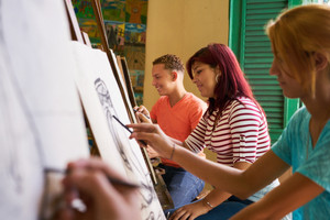 School of art, college of arts, education for group of young students. Happy latina woman smiling, girl learning to paint.