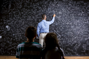 School teacher in front of big blackboard and his students