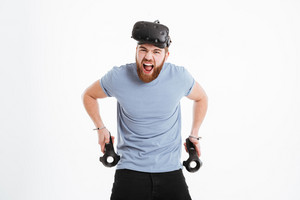 Screaming bearded man wearing virtual reality device standing over white background with joysticks. Look at camera.