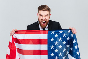 Screaming business man in black suit holding the USA flag with open mouth and looking at camera. Isolated gray background