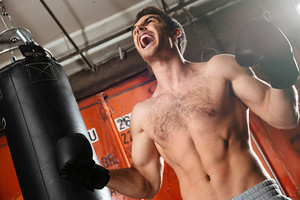 Screaming young boxer training in a gym with punchbag. Eyes closed.