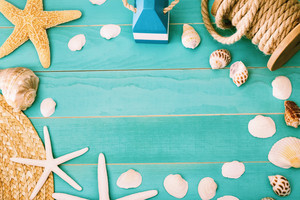 Sea shells and straw hat on light blue wooden background