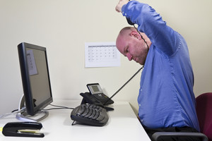 Self-destructive office worker / businessman try to strangle himself with the telephone cable.