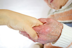 Senior and young holding hands over white background