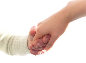 Senior and young women holding hands on white background