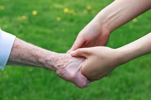Senior and Young Women Holding Hands Outside