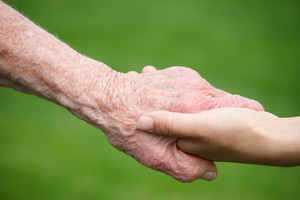 Senior and young women holding hands over green lawn background
