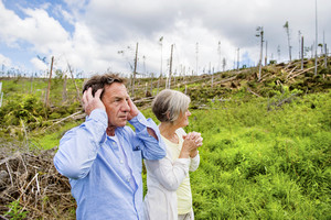 Senior couple at destroyed forest as an effect of strong storm in High Tatras, Slovakia