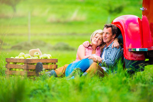 Senior couple harvesting fruit, sitting on grass at red vintage pickup truck, hugging