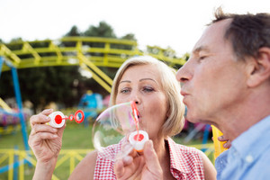 Senior couple having a good time at the fun fair, blowing soap bubbles with bubble wand.
