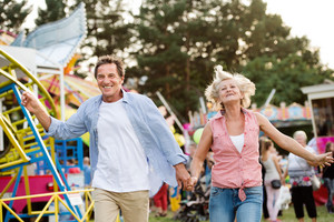 Senior couple having a good time at the fun fair, holding hands, running. Sunny summer day.