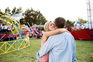Senior couple having a good time at the fun fair, hugging and kissing. Sunny summer day.