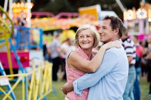 Senior couple having a good time at the fun fair, hugging. Sunny summer day.