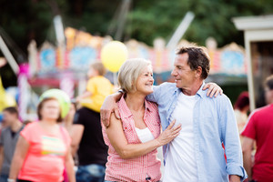 Senior couple having a good time at the fun fair, hugging. Sunny summer day.