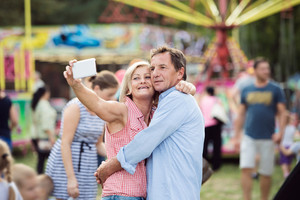 Senior couple having a good time at the fun fair, taking selfie with smart phone